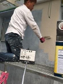 加古川市の外壁塗装工事の中塗り作業中の写真