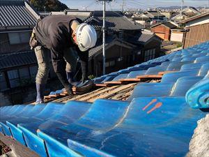 姫路市の屋根葺き替え工事の釉薬瓦撤去中の職人